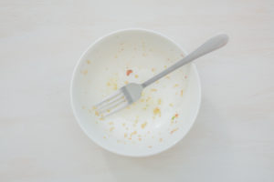 Rice scraps with vegetables in a white bowl on a white table